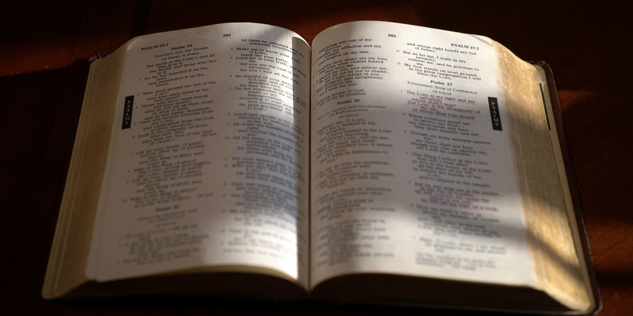 Open bible on a dark wood table with light and focus on Psalm 27